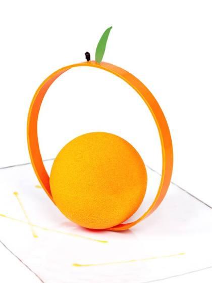 Le magnifique : sphère chocolatée orange garnie en son coeur d'éclats de sablés croquants mêlés de crème chantilly parfumée au caramel orange et de suprêmes d'oranges caramélisées. Crédit photo : Ladurée